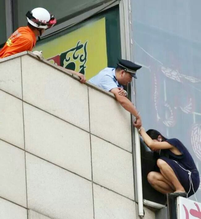 14. Beijing cop handcuffs himself to suicidal woman on ledge to save her life.