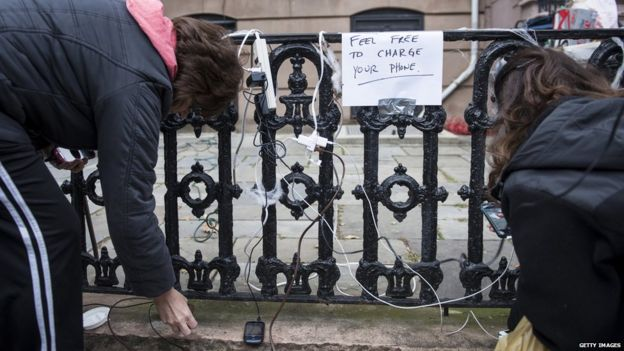 16. People charge their phones on the street after Hurricane Sandy in New York.
