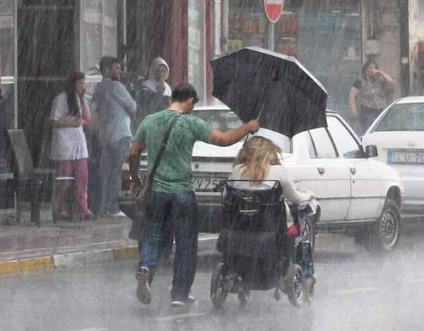 22. A man holds an umbrella for a woman in a wheelchair.