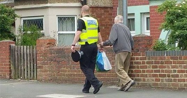 24. A Good Samaritan cop helping an old man with his heavy shopping.