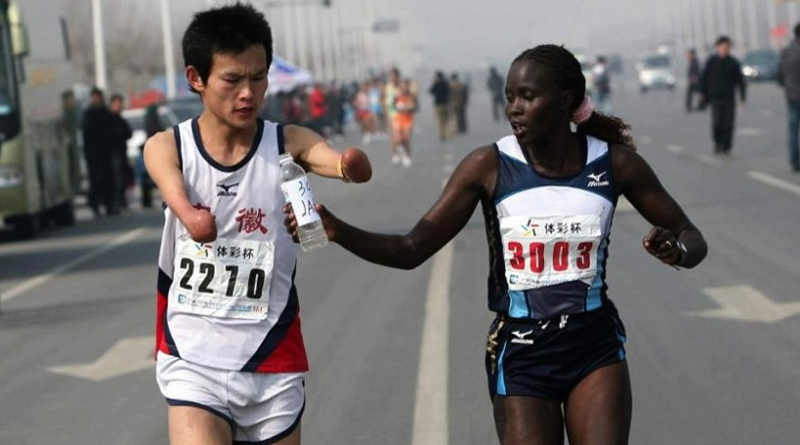 9. Kenyan athlete helps chinese man with no hands drink water.