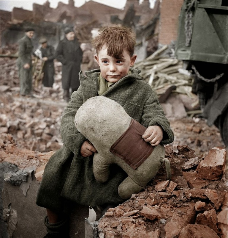 Abandoned boy holding a child's game, London 1945