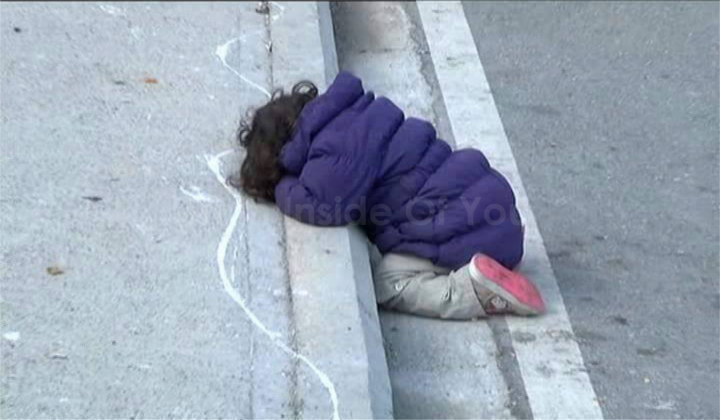 A refugee girl sleeping on the streets this afternoon in Greece