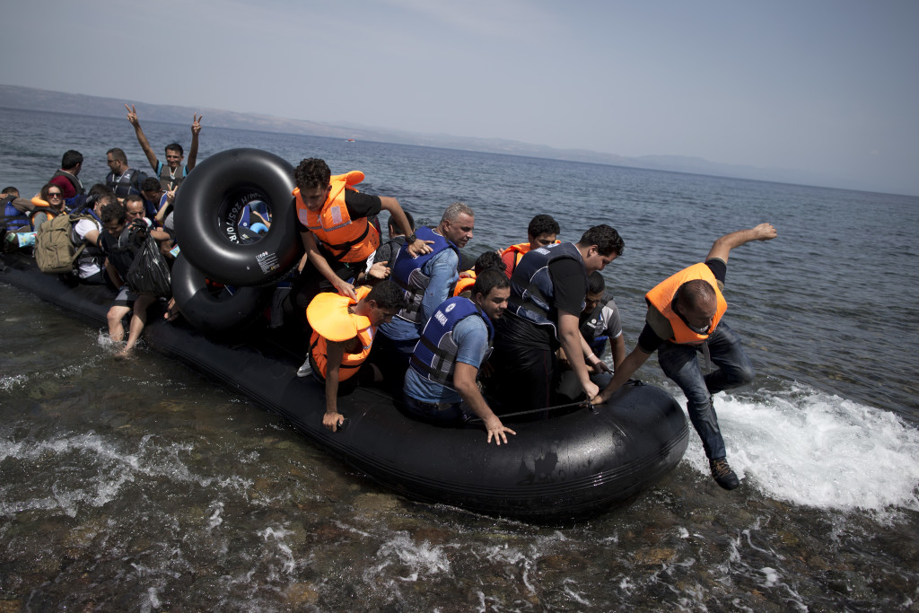 Syrian men, women and children arrive aboard a dinghy after crossing from Turkey, on the island of Lesbos, Greece, Monday, Sept. 7, 2015. The island of some 100,000 residents has been transformed by the sudden new population of some 20,000 refugees and migrants, mostly from Syria, Iraq and Afghanistan. (AP Photo/Petros Giannakouris)