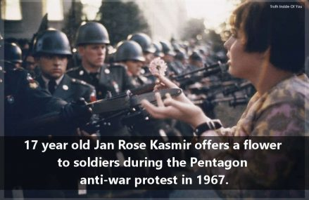 17 year old Jan Rose Kasmir offers a flower to soldiers during the Pentagon anti-war protest in 1967