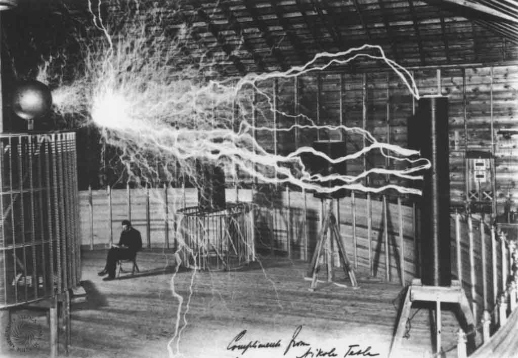 Tesla near his transmitter in Colorado Springs. The device was capable of transmitting millions of volts of electricity over great distances without wires. The image was taken in 1899.
