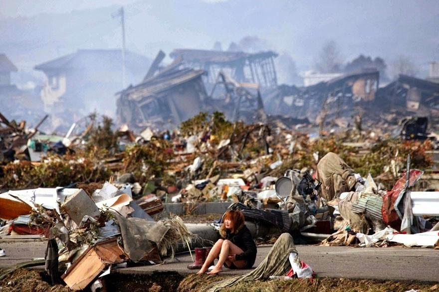 30 of the most powerful images of all time - A woman sits amidst the wreckage caused by a massive earthquake and ensuing tsunam, in Natori, northern Japan