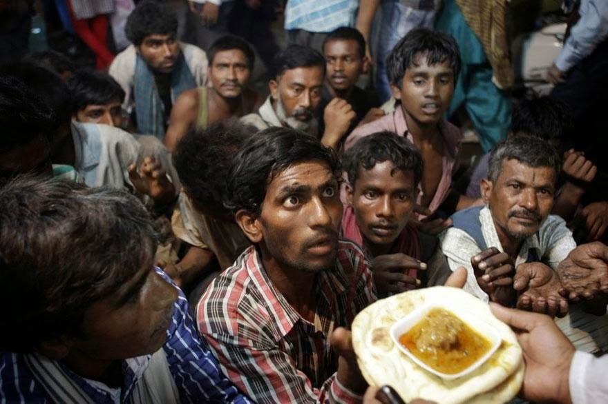 30 of the most powerful images of all time - Indian homeless men wait to receive free food
