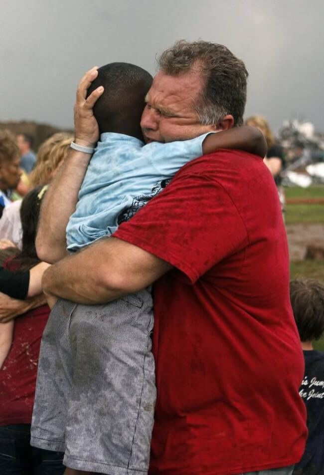 9. A teacher hugs a child at Briarwood Elementary school after a tornado destroyed the school in south Oklahoma City.