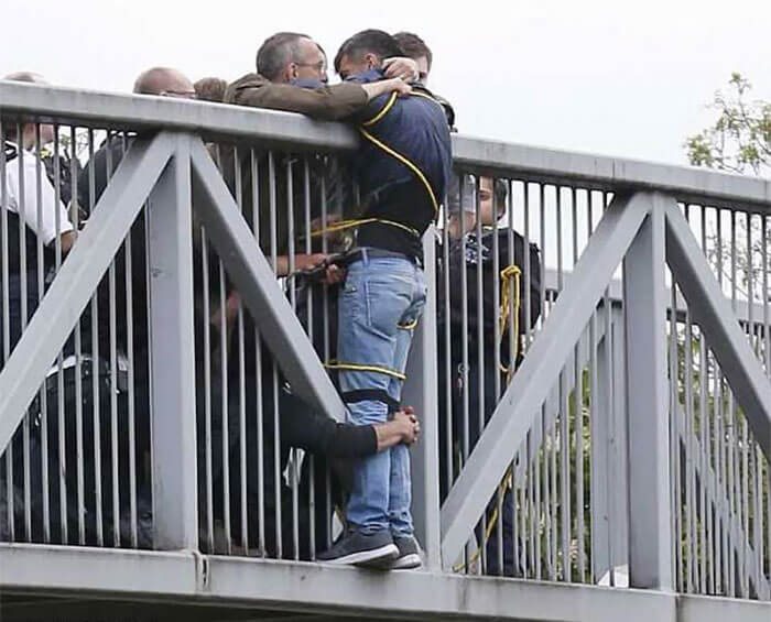 People Holding Onto Man Trying To Commit Suicide